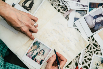Woman writing in a scrap book with  photos
