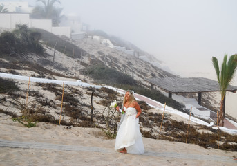 Bride Walking on Beach in Fog