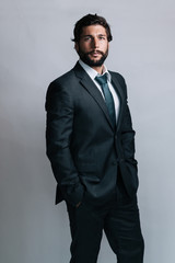 studio portrait of a standing full bearded businessman in a dark grey suit