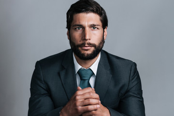 studio portrait of full bearded well dressed young business man looking in the camera