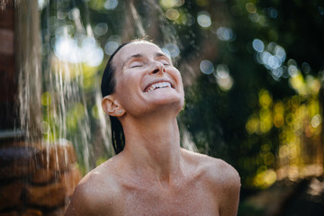 Beautiful woman in outdoor shower surrounded by nature