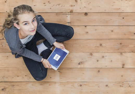 User with Tablet on Wooden Floor Mockup 1