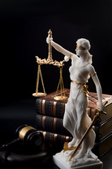 Legal code, enforcement of the law and blind Iustitia concept with statue of the blindfolded lady justice ( Dike in Greek and Justitia in Roman mythology), a stack of books and a gavel