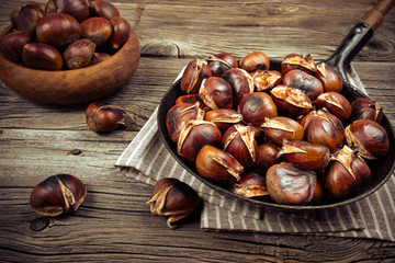 Fototapeta chestnuts in a pan on a wooden background obraz