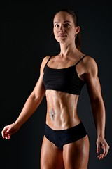 Beautiful young sporty sexy woman showing muscle