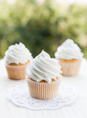 Vanilla cupcakes topped with swirl of sweet vanilla frosting captured on the wooden table in a sunny day.