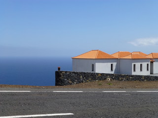 White houses with orange roof on La Palma in the foreground the road and in the background the sea