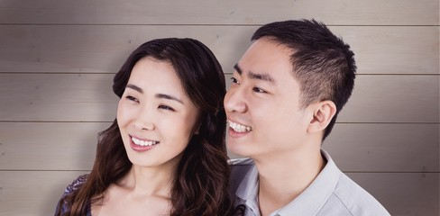 Composite image of cheerful couple looking away