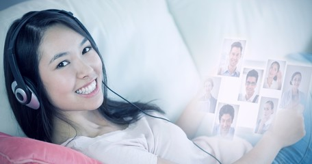 Composite image of girl using her tablet pc on the sofa and