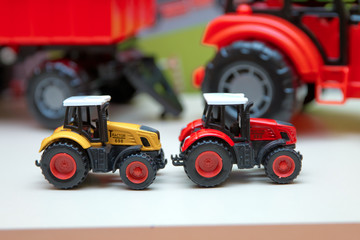Yellow and red traxtor toys in the background without focus