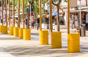 Yellow barrels on the waterfront of the city, Salou, Tarragona, Spain. Copy space for text.