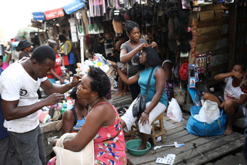 A woman gets her eyebrows done as another one gets her hair done in a street of Port-au-Prince