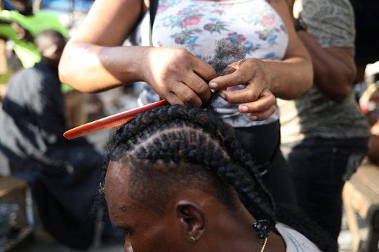 A hairdresser adds hair extensions to a man in a street of Port-au-Prince