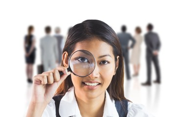 Composite image of businesswoman looking through magnifying
