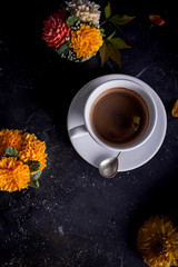 cup of coffee with cakes decorated with flowers on a black background with fresh flowers
