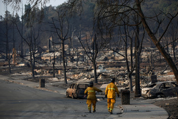 Firefighters walk in a neighborhood destroyed by the Tubbs Fire in Santa Rosa, California