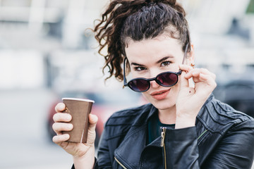 Beautiful girl drinks coffee on the street