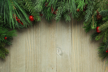 Christmas tree branches on wooden background