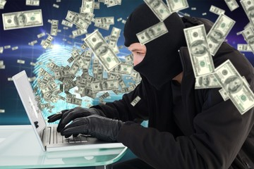Composite image of robber sitting at desk hacking a laptop
