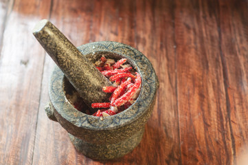 Cooking spicy thai sauce with chili pepper and sugar in Stone mortar with pestle on wooden table