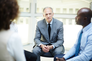 Attentive mature businessman listening to one of subordinates at business training