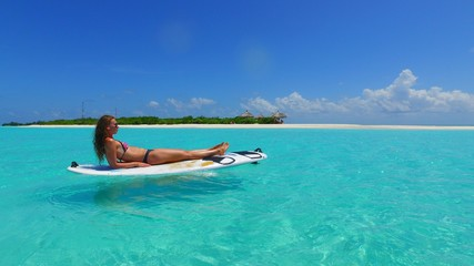 P02769 Maldives white sandy beach 1 people a young beautiful woman sitting relaxing on paddle board on sunny tropical paradise island with aqua blue sky sea water ocean 4k