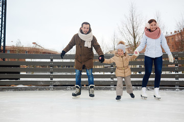 Happy couple and their daughter on skates moving down ice-rink in urban environment