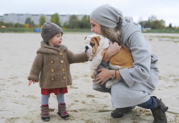Cute little girl plays with a puppy of a bulldog on the river bank in autumn