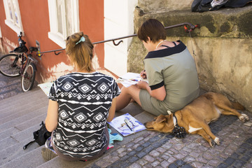 Czechia two women sit and drawing watercolor painting Prague city with dog sleep on pathway of Prague castle