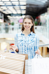 Female shopaholic with paperbags showing her purchases