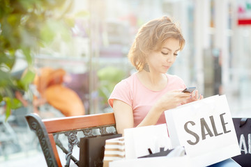 Young woman texting in smartphone while having rest after shopping
