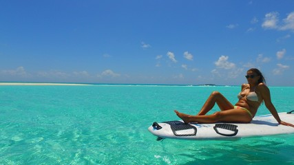 P02821 Maldives white sandy beach 1 people a young beautiful woman sitting relaxing on paddle board on sunny tropical paradise island with aqua blue sky sea water ocean 4k