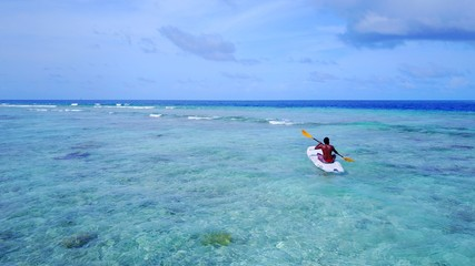 P02069 Aerial flying drone view of Maldives white sandy beach young man relaxing on paddleboard on sunny tropical paradise island with aqua blue sky sea water ocean 4k
