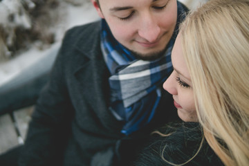 Glückliches Paar in Winterlandschaft sitzt auf Parkbank