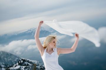 Junge blonde Frau mit weißem Kleid und Schleier tanzt auf dem Berg