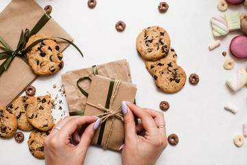Fond of sweets and Christmas gifts. Young woman preparing small presents on white table with colorful macaroons, zephyrs and chocolate scone nearby, top view picture