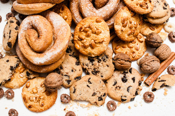 Culinary background of pastry shop, close up. Wholegrain cookies with peanuts and chocolate, baked roll with sugar powder on white table, top view. Delicious sweets and bakery, unhealthy food concept