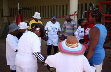 Grannies hold hands as they pray before taking part in boxing lessons in an attempt to battle old age with exercise at Cosmo city outside Johannesburg