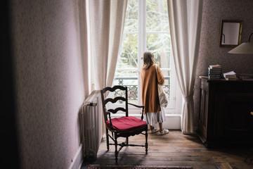 Petite fille de dos qui regarde par la fenêtre
