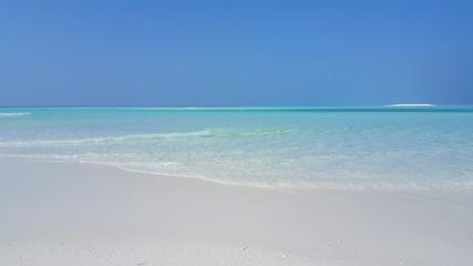 P02832 Maldives beautiful white sandy beach background on sunny tropical paradise island with aqua blue sky sea water ocean 4k