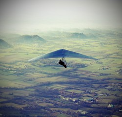 man flying high with his hang glider above the plain