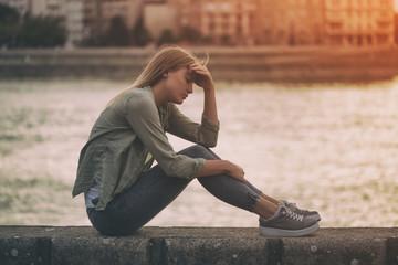 Sad woman sitting at the riverbank.