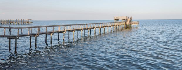 Fishing piers stretching out over Galveston Bay in Kemah, Texas, USA. Foot pier for saltwater fishing of vacation home/beach house rental/bay home in Lighthouse District waterfront at sunset. Panorama