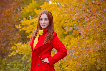 Portrait of the young beautiful woman in a red casual coat and red-yellow scarf walks in autumn park. Pretty view of walking woman outside