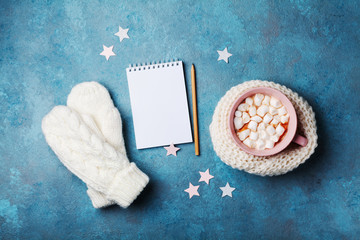 Cup of hot cocoa decorated knitted scarf with marshmallow, mittens and clean notebook on turquoise table top view. Flat lay style. Winter mockup.