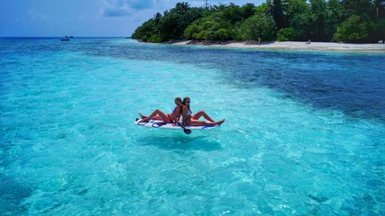P02092 Aerial flying drone view of Maldives white sandy beach 2 people young woman relaxing on paddleboard on sunny tropical paradise island with aqua blue sky sea water ocean 4k