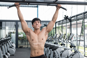 young man execute exercise with machine in fitness center. male athlete training in gym. sporty guy working out in health club.