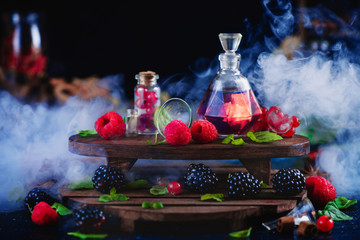 Raspberry and blackberry perfume in a vintage bottle. Dark still life with wintage wooden shelves and fresh berries. Aromatic laboratory concept, magical still life with smoke.