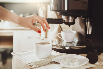 Woman making fresh espresso in coffee maker. coffee machine makes coffee.