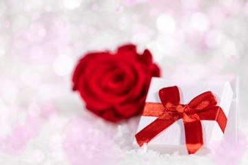 Geschenk mit roter Schleife und Rose vor glänzendem Hintergrund mit Herzen